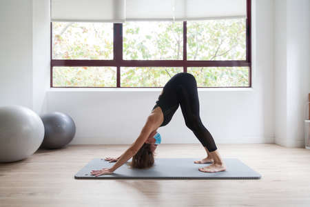 Sporty woman practicing yoga wearing protective mask Stockfoto