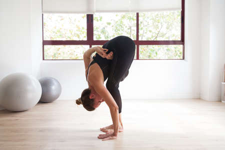 Sporty woman practicing yoga in a bright loft studio