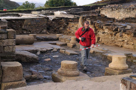 Archaeologist taking photos  in the patio of the ' Domus ' Archaeological site ' Chao Samartin ' Asturias SPAIN