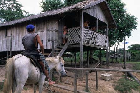 mujer:  Man on horseback against  stilts. Camutins MARAJO ISLAND (Amazon). BRAZIL
