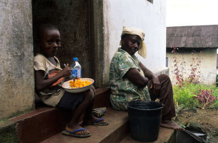 EQUATORIAL GUINEA. South Bioko. BATETE ; Child eating in front of his house.
