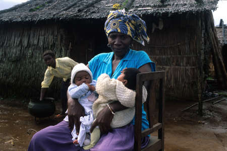 world village: EQUATORIAL GUINEA. South Bioko. MOCA ; Women with babies on their doorstep. Editorial