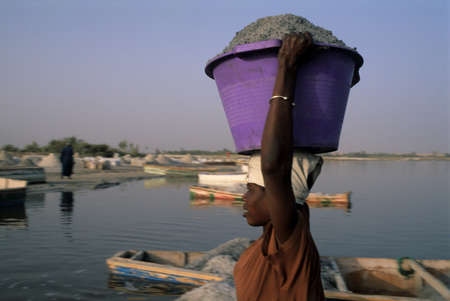 third world economy: Woman carrying bucket of salt in the head. LAC ROSE  ( Retba ) Dakar Region SENEGAL Editorial