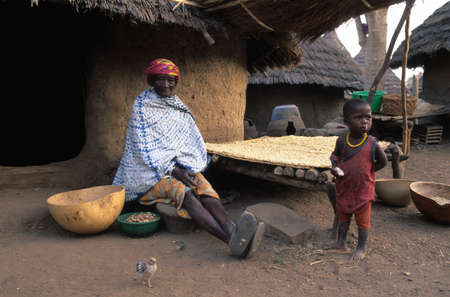 ancestral: SENEGAL. Tambacounda Region   ( Bassari Country )  BEDIK    Village of Iwol   ;  Woman drying corn in front of his hut.