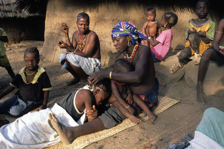 SENEGAL. Tambacounda Region  ( Bassari Country )  BEDIK    Village of Iwol  ; Woman preparing the boy for  Feast of the Initiation