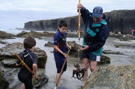 praia: Boys learn fishing octopus    PRAIA AS CATEDRAIS  -  RIBADEO COUNCIL.  Province of  Lugo.  Galiza . SPAIN