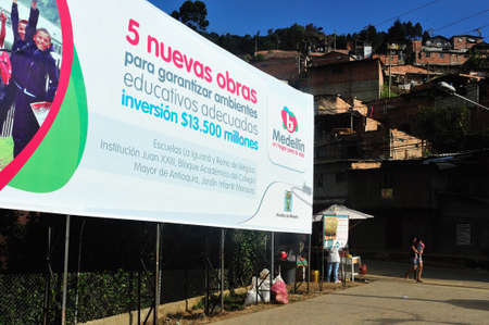 comunas: Sign with information about the ALCALDIA investment in improving education - Santo Domingo district  in MEDELLIN .Department of Antioquia. COLOMBIA Editorial