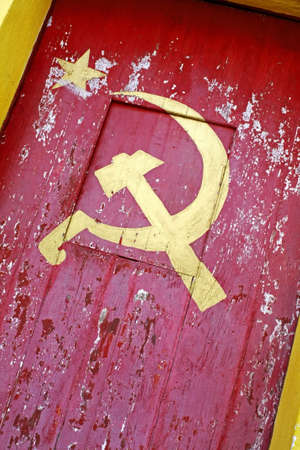 ideology: Communist symbol painted in a old scraped painted door in the branch office of the party Stock Photo