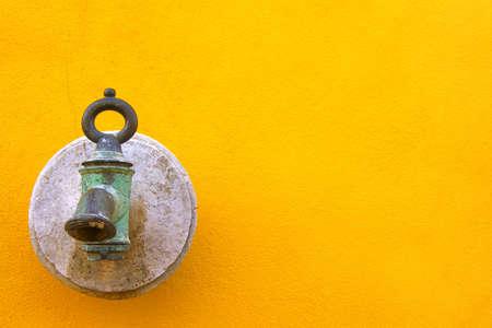 waterspout: Vecchio waterspout metallico su sfondo giallo