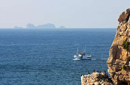 Trawler at sea of Peniche with the Berlengas island in the horizon line Stock Photo - 8347242