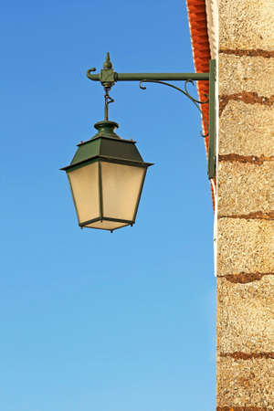 Ancient wall street green lamp with blue sky as background photo