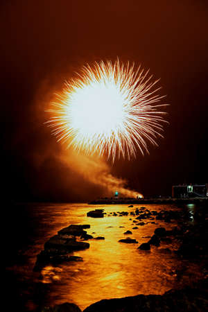 Orange fireworks launched at the shoreline of the harbor photo