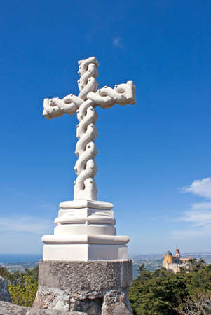 Beautiful  Christian cross carved in stone with interlaced effect located at the highest point of the Sintra hills overlooking the palace of Pena (Cruz Alta) photo