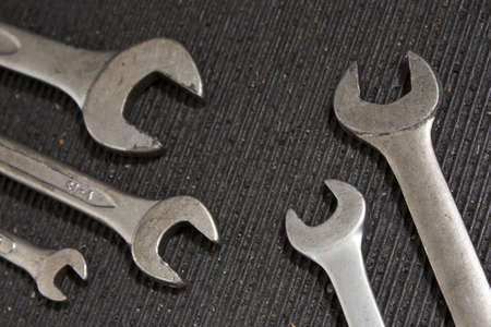 Set of used wrenches in a dirty black rubber mat photo