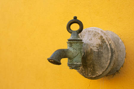 nascent: Ancient faucet in bronze in a yellow wall Stock Photo