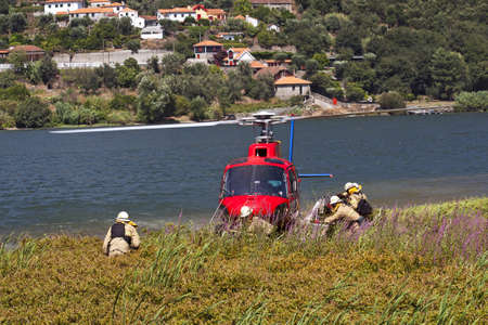 Crew of firefighters working on the helicopter stopped on the banks of the River Douro photo