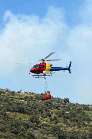 Firefighting helicopter carrying water to extinguish the fire photo