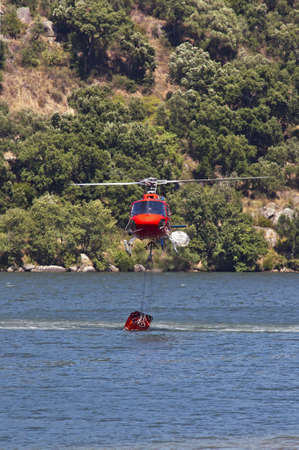 tree world tree service: Firefighting helicopter collecting  water in the Douro river  to extinguish the forest fire
