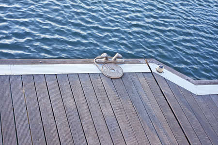 A folded spiral mooring rope with a end knot around a cleat on a wooden pier photo