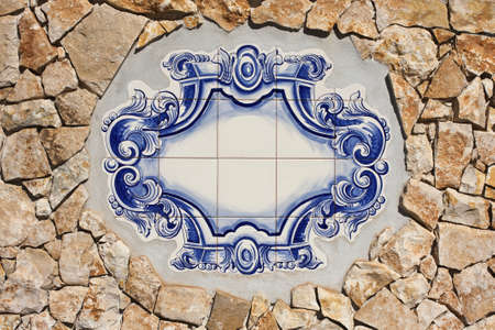 Information panel of traditional Portuguese tiles hand-painted blue and white, placed in a rustic stone wall Orange photo
