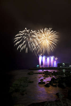 Purple and white fireworks on the beach photo