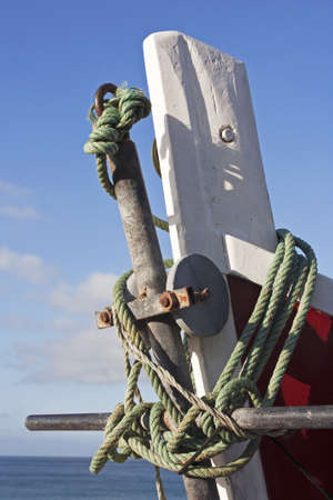 Prow of a wooden white and red fishing boat with the anchor tied with a green string. The sea, clouds and blue sky as background photo