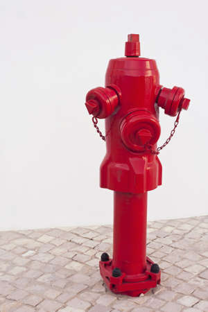 A red metallic fire hydrant in the ground for fighting urban fires photo