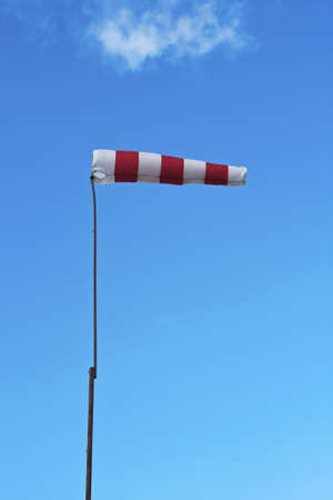 Windsock  with white and red stripes isolated on a blue sky as background photo