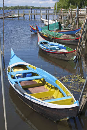 Ancient traditional boats of fishermen anchored in a wooden wharf of Tagus river in Escaroupim, Portugal photo
