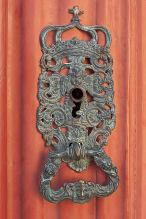 Ancient lock with religious icon details in an orange wooden door of a church photo