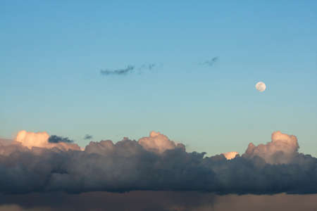 overcast: Full moon and clouds illuminated by sun at the end of the day