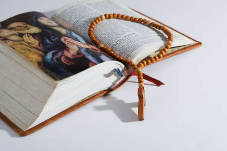 Wooden rosary of Catholic Prayer on an old holy Bible Stock Photo
