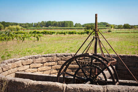 Old Noria in iron on the Green agricultural fields Stock Photo