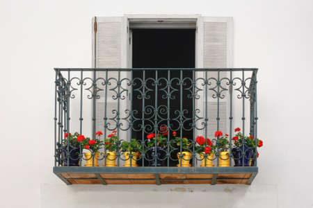 An iron balcony with red flowers in Tarifa, south of Spain Stock Photo