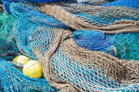 Colorful fishing nets rolled with two small yellow buoys