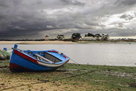 Bateau traditionnel de la région de Lisbonne, amarré sur la plage, à marée basse