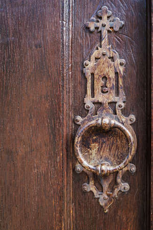 Old metal lock knocker, with a christian cross, on a door of wood Foto de archivo