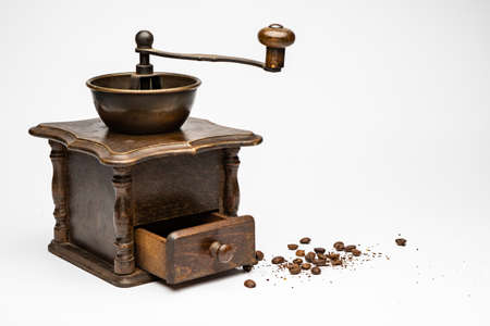 Old coffee grinder with small cofee beans at side and white background 版權商用圖片