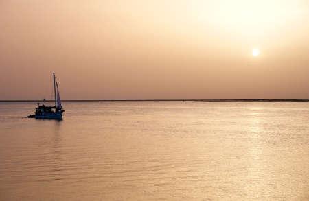 region of algarve: Recreation boat at sunset, in Ria Formosa, natural conservation region in Algarve, Portugal.