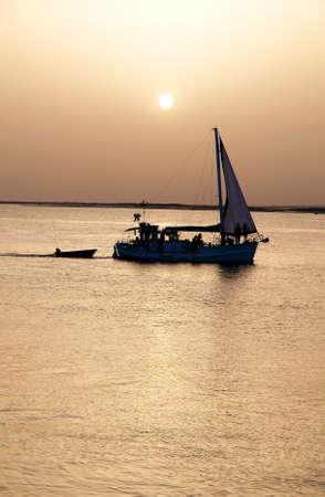 region of algarve: Recreation boat at sunset, in Ria Formosa, natural conservation region in Algarve, Portugal