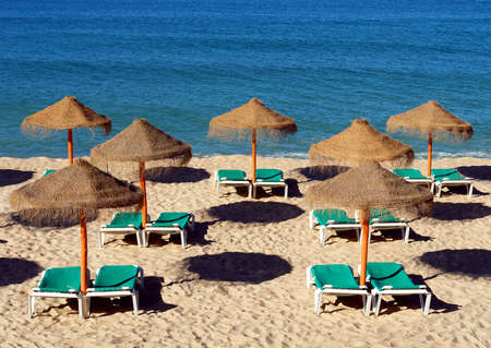 loungers: Parasol and sun loungers on the beach sand Stock Photo