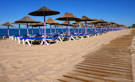 Parasol and sun loungers on the beach sand photo