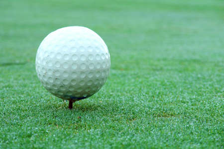 Golf course tee marker, ball shaped over lawn background photo