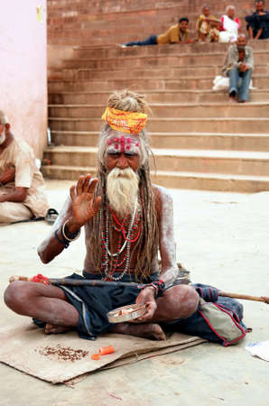 VARANASI, INDIA - SEPTEMBER 21, 2009: An Indian holy pilgrim sits on the banks of the Ganges in Varanasi. India.