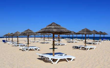 loungers: Parasol and sun loungers on the beach sand, Tavira island, Algarve  Portugal Stock Photo