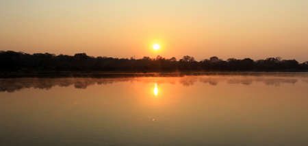 Sunrise at Kavango river whit mist on the water surface, Caprivi region. Namibia photo