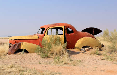 abandoned gas station: Old and rusty car wreck at the last gaz station before the Namib desert. Solitaire, Namibia. Stock Photo