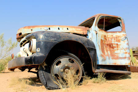 rusty car: Old and rusty car wreck at the last gaz station before the Namib desert  Solitaire, Namibia