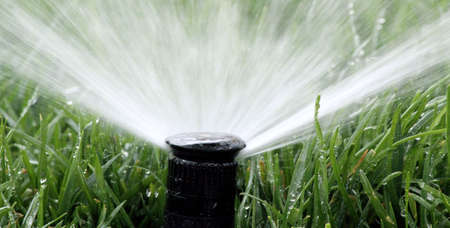 irrigate: Automatic Garden Irrigation Spray watering lawn Stock Photo