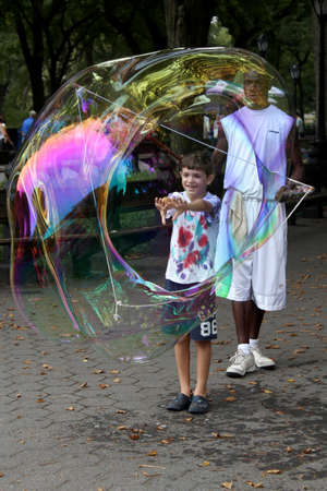 NEW YORK - SEPTEMBER 01  Unidentified performer and kids play with soap bubbles at Central Park, on September 01, 2013, in New York City